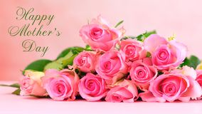 Pink roses on pink wood table, Mother`s Day background closeup. Pink roses on pink wood table, Happy Mother`s Day background closeup with greeting message text Royalty Free Stock Images