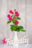 Pink roses and wooden family word stock photo
