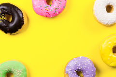 Pink round donut and few other on yellow background. Flat lay, top view. Stock Image