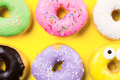 Pink round donut and few other on yellow background. Flat lay, top view. Stock Photo