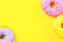 Pink round donut and few other on yellow background. Flat lay, top view. Royalty Free Stock Images