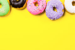 Pink round donut and few other on yellow background. Flat lay, top view. Royalty Free Stock Photography