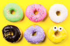 Pink round donut and few other on yellow background. Flat lay, top view. Stock Photos