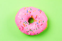 Pink round donut on green background. Flat lay, top view. Stock Photography