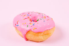 Pink round donut on pastele background. Flat lay, top view. Royalty Free Stock Image