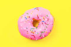 Pink round donut on yellow background. Flat lay, top view. Stock Image