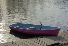 Pink rowing boat moored by the jetty pier on a lake Royalty Free Stock Image