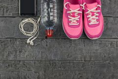 Beautiful pink sneakers, headphones, water and apples on a wooden dark floor. View from above. royalty free stock photos