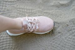 Pink runnung shoes one side stamp on sand with shoes prints royalty free stock photos