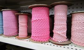 Pink S shape wave lace coils on shelf. Pink S shape wave lace coils on storage shelf Stock Photo