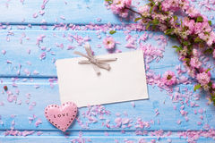 Pink  sakura flowers, empty tag and  heart on blue wooden planks Stock Images