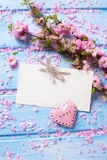 Pink  sakura flowers, empty tag and  heart on blue wooden planks Stock Image