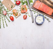 Pink salmon fillet with tomatoes, rosemary, curd cheese, vintage cutlery and sandwiches border, place for text  on wooden rustic b Royalty Free Stock Images