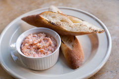 Pink salmon rillette. Pate of smoked fish in white plate, grilled baguette. soft focus, closeup. Pink salmon rillette. Pate of smoked fish in white plate Stock Photos