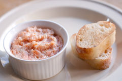 Pink salmon rillette. Pate of smoked fish in white. Plate, toasted baguette bread. soft focus, closeup Stock Image