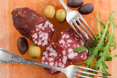 Pink salt block with salami, green and calamata olives and fresh. Rocket salad served with vintage melchior forks overhead view Royalty Free Stock Photography