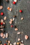 Pink salt grains and peppercorn on wooden table Stock Photos