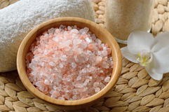 Pink salt from the Himalaya. Closeup of pink SPA salt in wooden bowl with orchid flower and towel Royalty Free Stock Photo