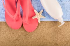 Pink sandal flip flop on blue towel and suntan cream lotion on sand beach and starfish. Beautiful female pink gently sandal flip flop on blue towel and suntan stock image