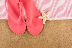 Pink sandal flip flop and towel on sand beach and starfish. Beautiful female pink gently sandal flip flop and towel on sand beach and starfish. Summer vacations stock photography