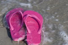 Pink Sandals. On the Beach with Wave Washing Over Stock Images