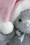 Pink Santa hat on teddy bear. A closeup of a silver teddy bear wearing a pink Santa hat Royalty Free Stock Photography