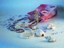 Pink sashet with pink and white beads and seashells. White shell and placer pearl beads from pink packing and starfish,Scattered blue beads and white shell Stock Photos