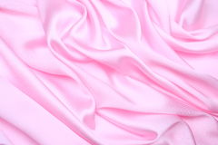 Pink satin background. A shining pink fabric used  for background Royalty Free Stock Photo