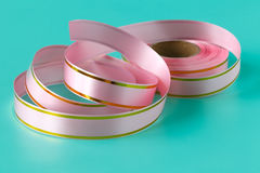 Pink satin  colored ribbons. On blue Royalty Free Stock Image