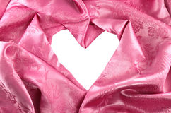 Pink satin fabric , heart. Pink satin fabric with beautiful patterns of folds Stock Photos