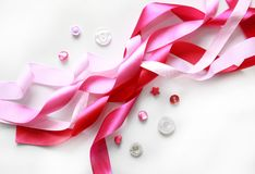 Pink satin ribbon and buttons. On white background Royalty Free Stock Photo