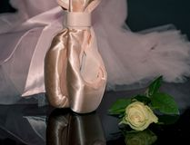 Pink satine ballet pointe shoes on black reflective backgeound w stock images