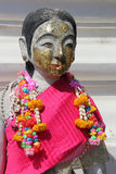 A pink scarf and flower garlands decorate the statue of a deity (Thailand) Royalty Free Stock Images