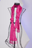 Pink scarf woven with fringes on a mannequin. On white background Stock Photo