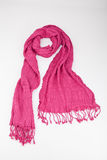Pink scarf woven with fringes on white background. Pink woven fringed scarf tied on white background Royalty Free Stock Image