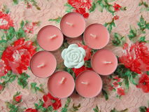 Pink scented candles with white flower in the middle. On flower background Royalty Free Stock Photo