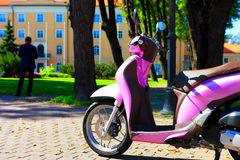 Pink scooter on background Palace in Riga Royalty Free Stock Photography
