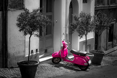 Pink scooter parked in narrow old street of Rome. One of the most popular transport in Italy, vintage Vespa royalty free stock photo
