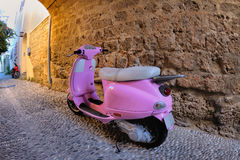 Pink scooter at a stone wall, Rhodes Stock Photography