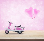 Pink scooter toy with pinkl heart love balloon on wooden table o Stock Images