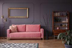 Pink settee against grey wall with mockup of gold frame in elegant living room interior. Real photo royalty free stock photo