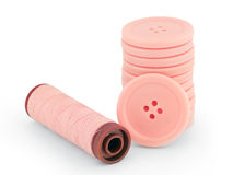 Pink sewing buttons and thread isolated royalty free stock image