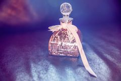 Pink Shabby Chic Glass Bottle with Lace and Key on Dark Leather stock photo