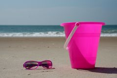 Pink shades and bucket on the beach. Pink sun glasses and pail sitting on the beach with waves in the distance stock images