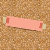 Pink sheet of paper for notes taped to a corkboard Royalty Free Stock Photo