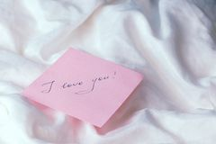 A pink sheet of paper with the words `I love you` on white crumpled fabric.  Royalty Free Stock Images