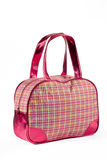 Pink shiny bag. Checkered multicolored bag with pink leather handles and corners Stock Image