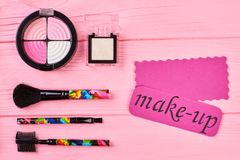 Pink shiny eyeshadows on colorful background. Set of cosmetics and brushes for make up. Pink card with text make-up Royalty Free Stock Image