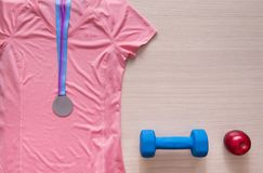 pink shirt, red apples, sports, clothing, top view, medal, dumbb Stock Photos