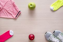 Shirt, sneakers, socks, apples, sport, flat lay Stock Photography